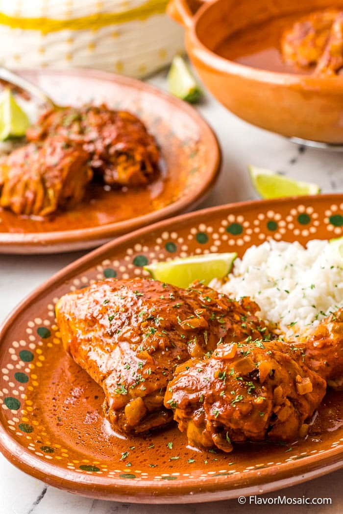serving dish with 2 pieces of pollo pibil with rice and a lime wedge. A second plate with an orange plate and bowl in the background.