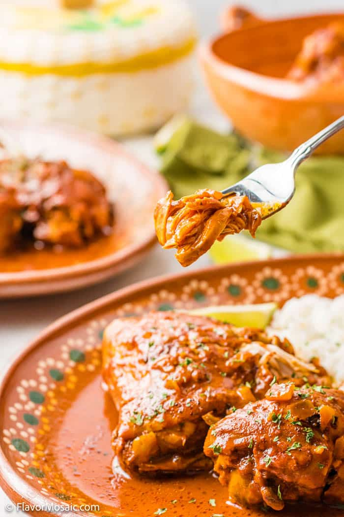 A fork with a bite of pollo pibil held above a dinner plate with the pollo bible and white rice with slice of lemon. A green napkin and a partial view of a and plate of pollo pibil is in the background.