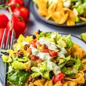 Salad plate with Taco Salad surrounded by Fritos and covered with Cilantro Lime Dressing with tomatoes and another salad plate with taco salad in back.