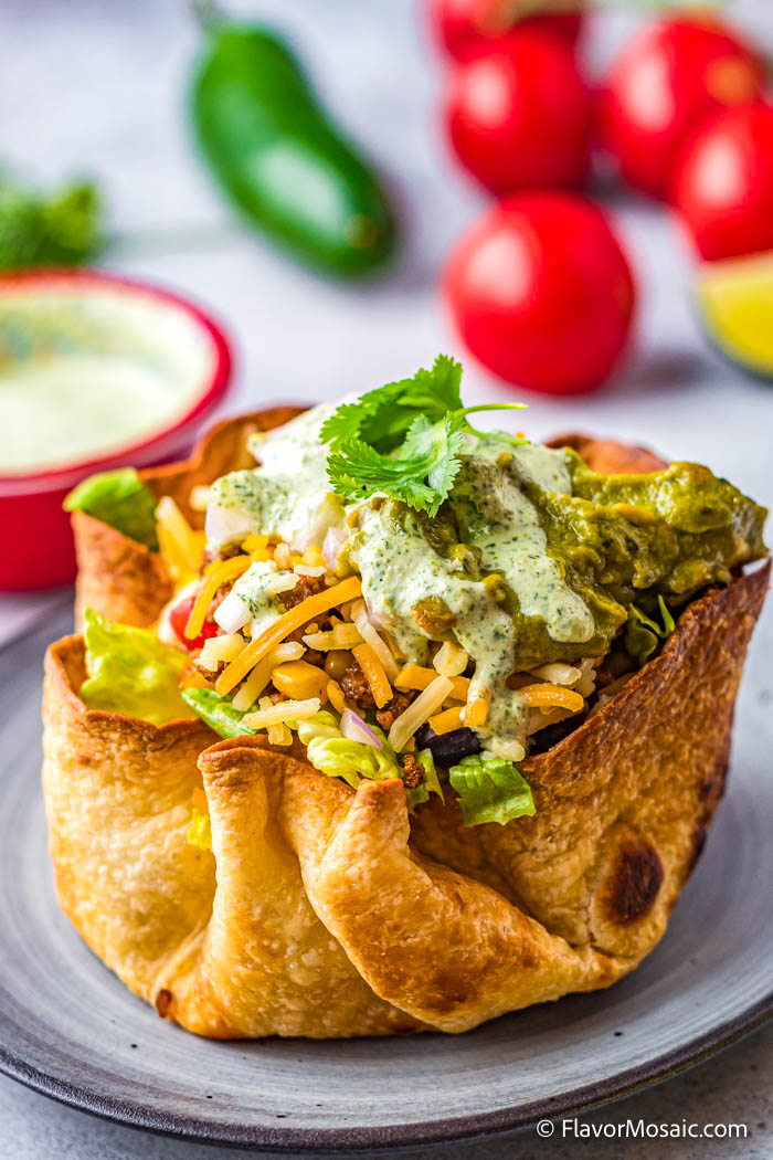 Taco Salad with Cilantro Lime Dressing inside a homemade Taco Bowl on a blue-gray plate with a small red bowl of more cilantro lime dressing and a jalapeno and cherry tomatoes in the background.