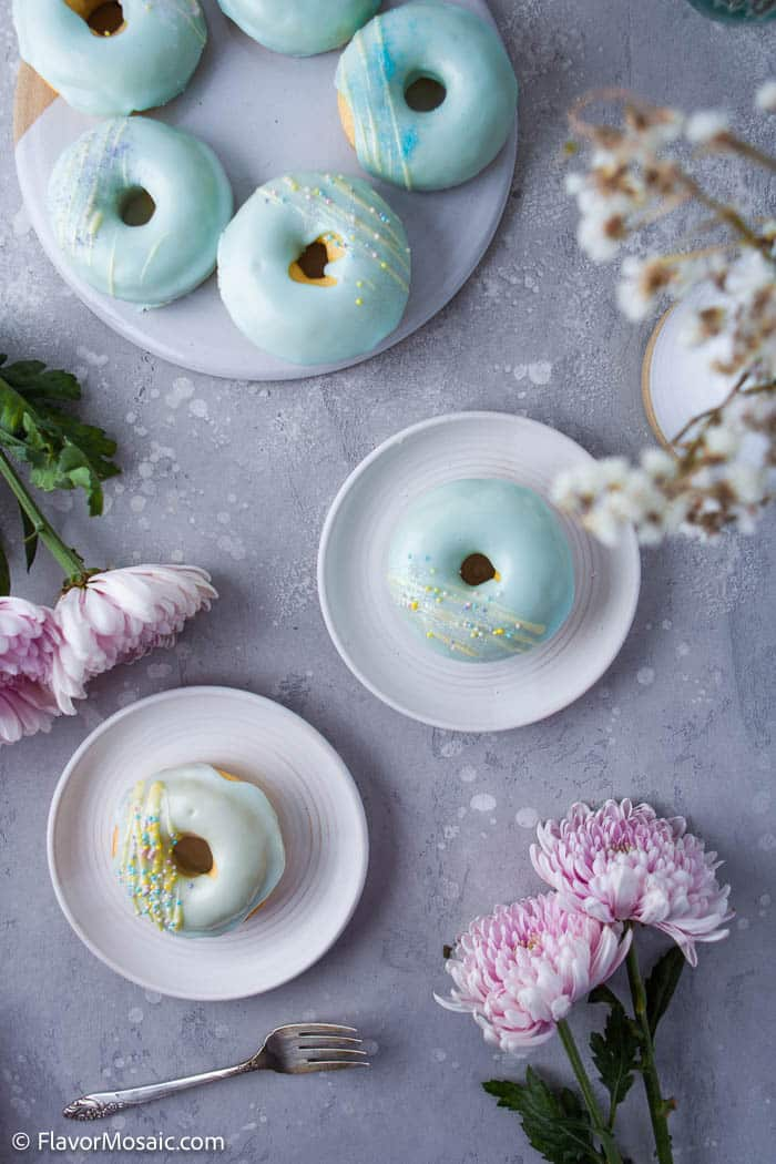 Overhead view of plate with 5 blue glazed donuts with yellow glitter and 2 small plates each with 1 blue glazed donut with yellow glitter surround by pink flowers and small white flowers on the top right corner of the photo.