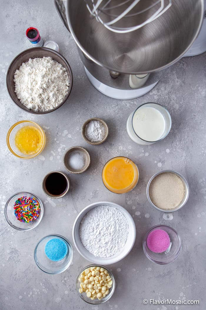 Overhead view of stand mixer next to individual bowls of ingredients for Vanilla Frosted Donuts with a glass of milk.