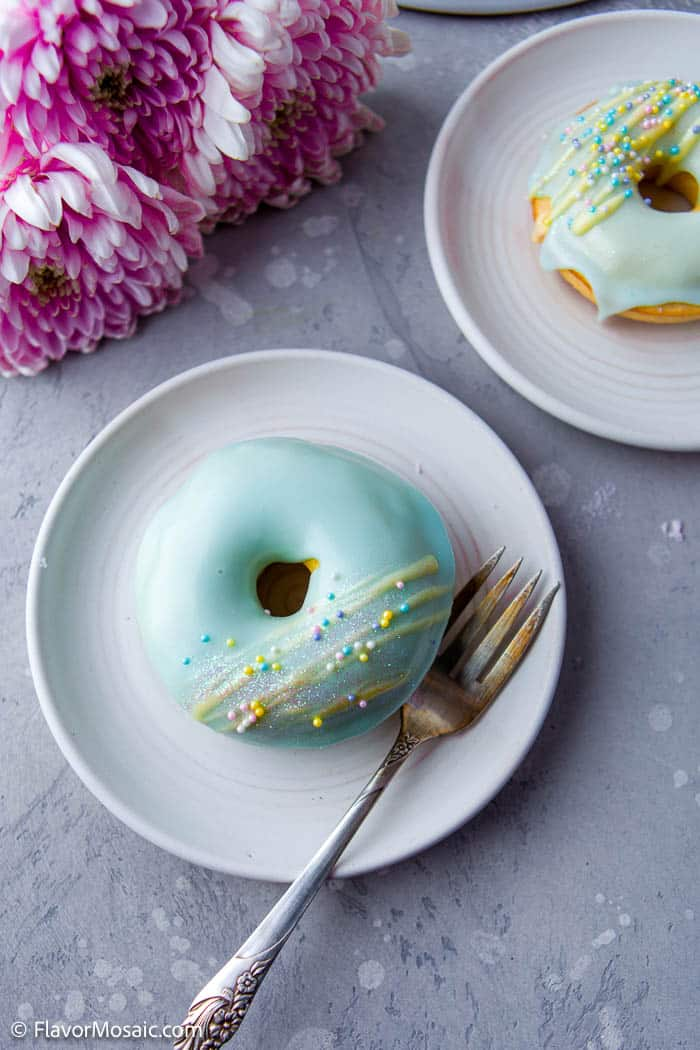 Overhead view of a small white plate with single Vanilla Frosted Donut with fork and partial view in top right of another white plate with donut with teal blue frosting and yellow glitter with a partial view of 3 pink flowers in the top left corner.