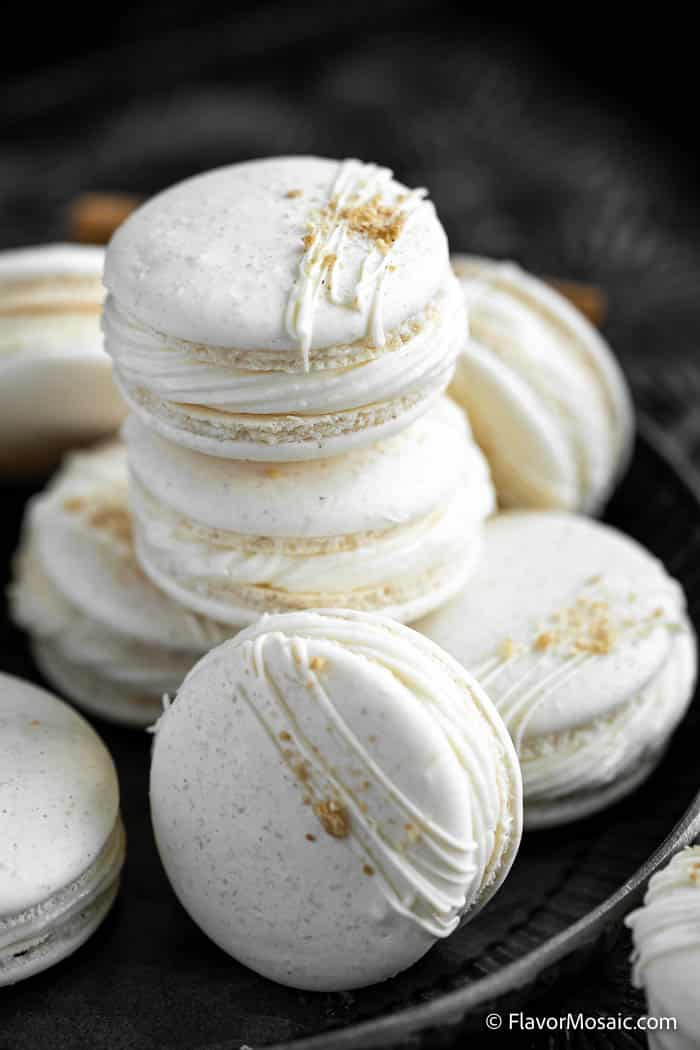 Stack of Apple Pie Macarons Recipe on black plate with black background.