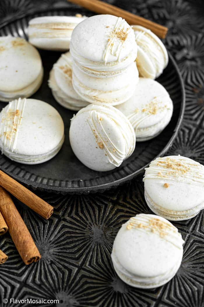 Stack of Apple Pie Macarons piled on a black plate with 2 cooks next to the plate and cinnamon sticks in the front left and in the back.