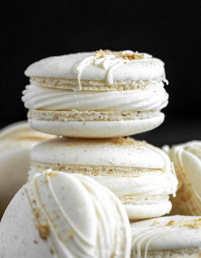 Side view of a stack of Apple Pie Macarons against a black background.