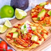 BBQ Chicken Tostadas on a cutting board surfing by tomatoes, limes, and avocado.