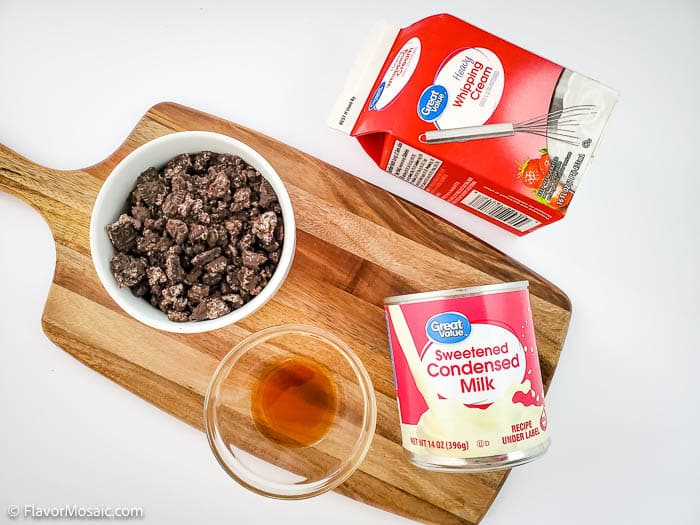 Overhead view of ingredients for cookies and cream ice cream on a wood cutting board, which includes a small bowl of chocolate chips, a small glass bowl of vanilla extract, a box of heavy whipping cream, and a can of sweetened condensed milk.