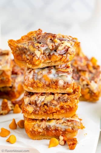 4 Pumpkin Magic Bars stacked on top of each other with more pumpkin bars in the background.