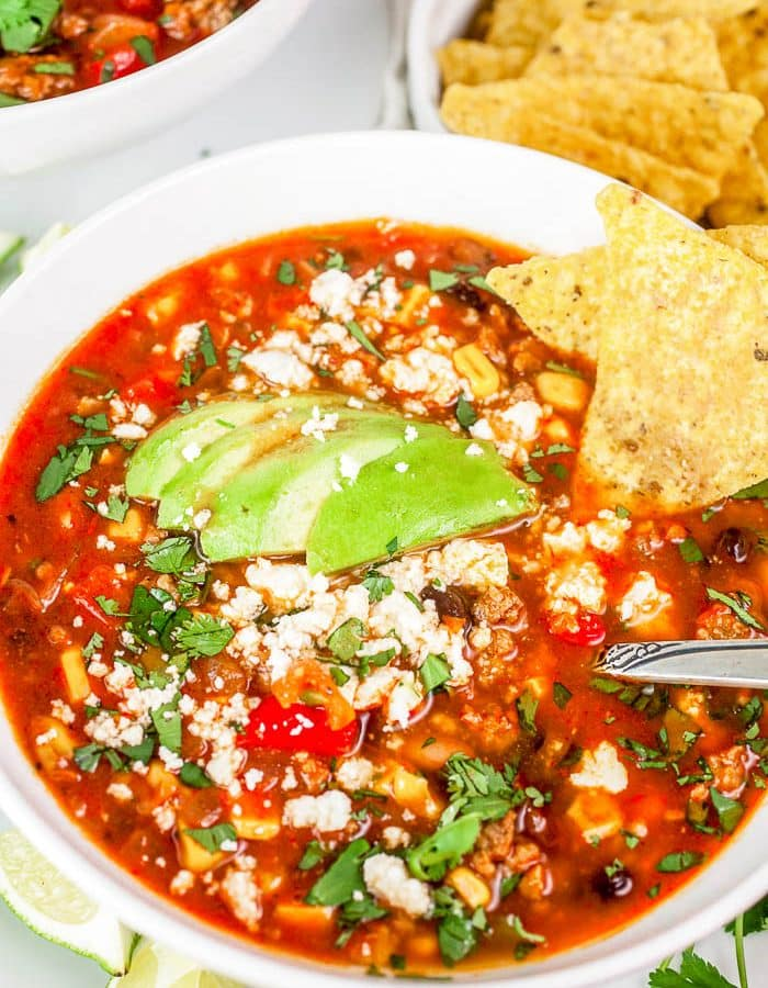 Overhead view of white bowl with Turkey Taco Soup with cheese crumbles, chopped cilantro, avocado slices and tortilla chips, and the bowl is surrounded by limes, tortilla chips, cilantro, and a partial view of a second bowl in the upper left corner.