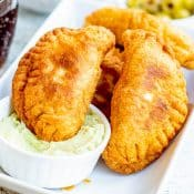 Photo of stack of Vegetarian Empanadas with one dipped into a small white bowl of avocado sauce.