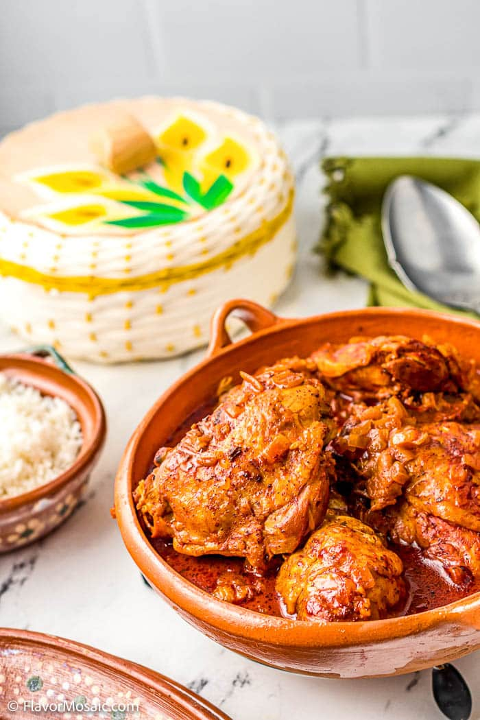 Saucy Pollo Pibil (AK Achiote Chicken or Chicken Pibil) in an orange bowl covered with achiote sauce.