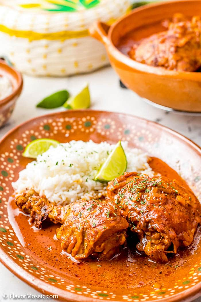 Orange Plate with 2 pieces of Achiote Chicken (or pollo pibil) covered with sauce with cilantro lime rice.