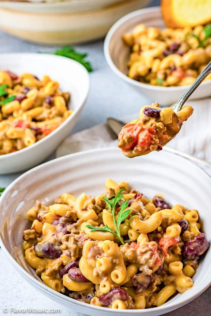 A small spoonful of Instant Pot Chili Mac held above a white bowl of chili mac with a white napkin and 2 white bowls with more chili mac.
