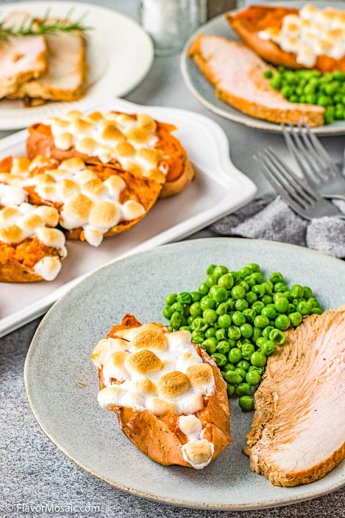 Plate with turkey, peas, and twice baked stuffed sweet potatoes topped with marshmallows, with a platter of the sweet potatoes, and a partial view of another dinner plate in the background.