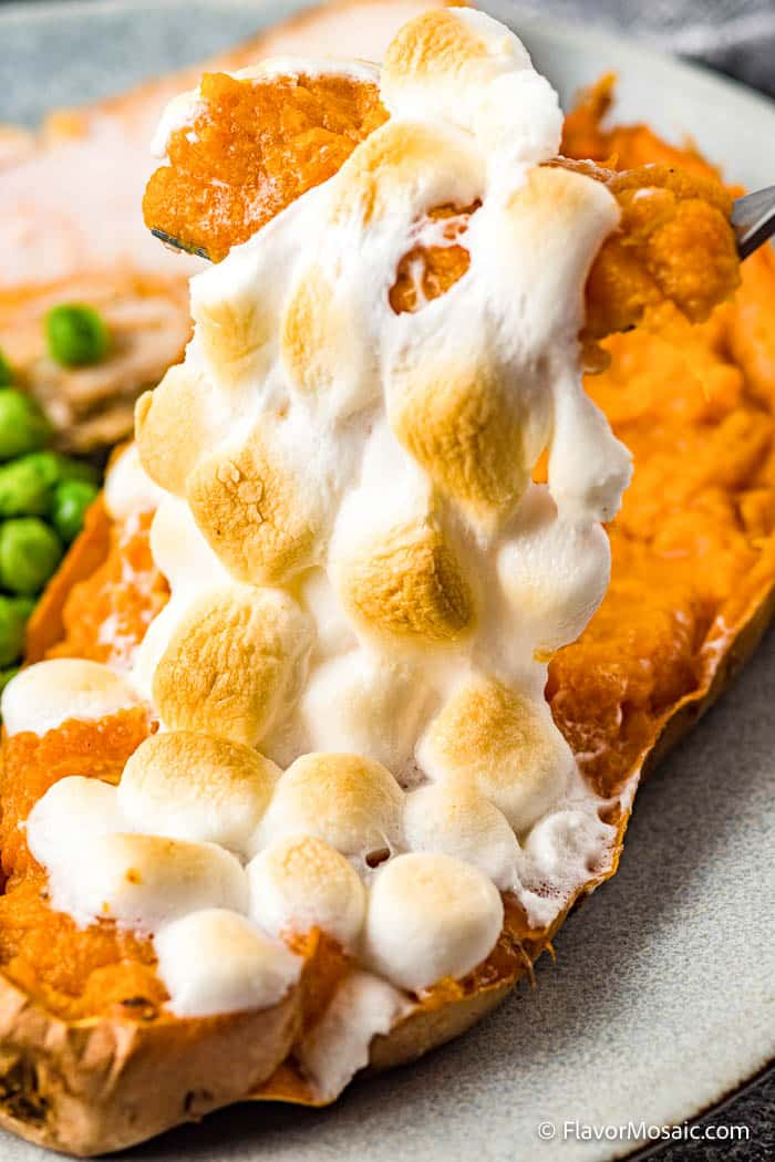 Photo of a Twice Baked Sweet Potato with Marshmallows showing a spoon of the twice baked sweet potatoes being held over the sweet potato with roasted golden brown marshmallows stretching from the spoon above to the sweet potato below.