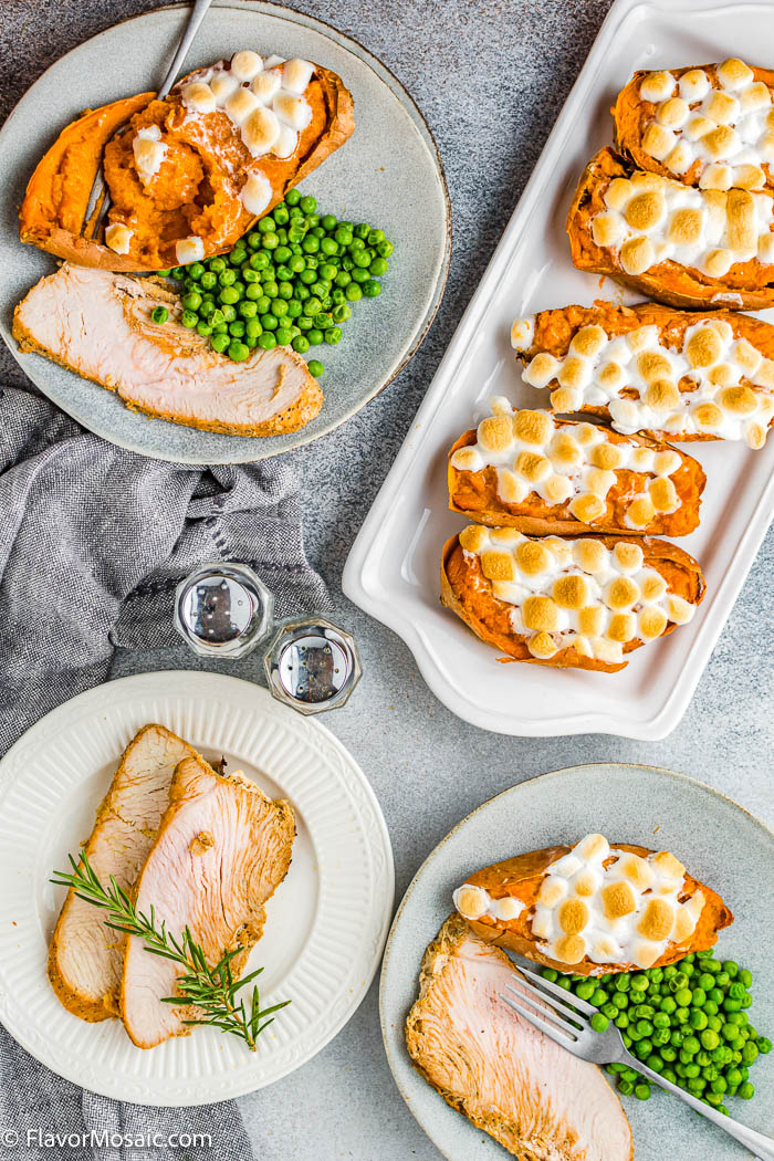 Overhead view of serving dishes on table with a platter of Twice Baked Stuffed Sweet Potatoes with marshmallows, 2 dinner plates with turkey, peas, and twice baked sweet potatoes, and another plate with 2 slices of turkey.