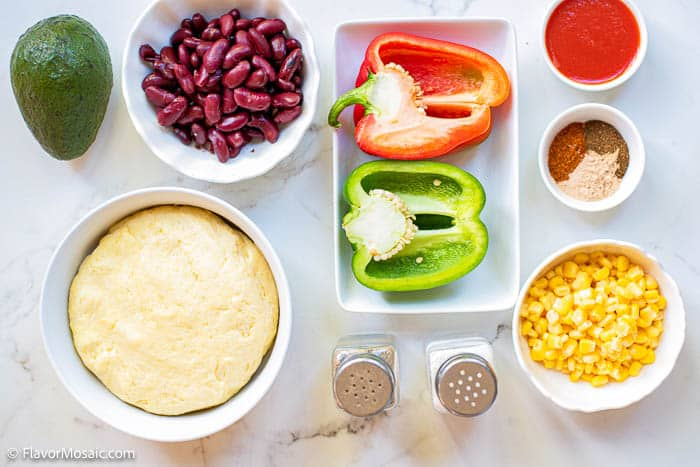 Overhead view of ingredients in separate bowls for vegetarian empanadas.
