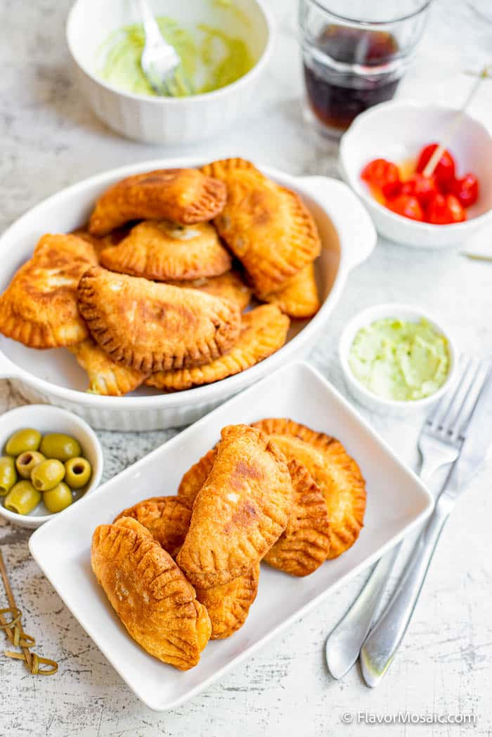 Overhead view of 2 dishes of vegetarian empanadas (savory hand pies) with a small bowl of olives and a small bowl of avocado cashew dip next to it.