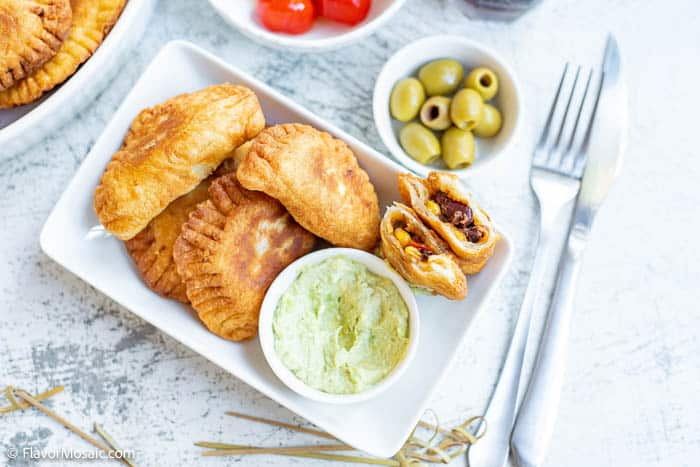 Horizontal overhead view of a small platter of empanadas, one cut in half with both sides standing up so you can see the inside of the empanada next the avocado cashew dip, with a small bowl of olives and a knife and fork.