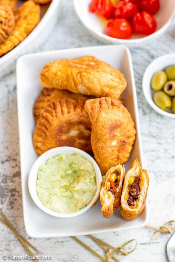 Vertical overhead view of a small platter of empanadas, one cut in half with both sides standing up so you can see the inside of the empanada next the avocado cashew dip, with a small bowl of olives.
