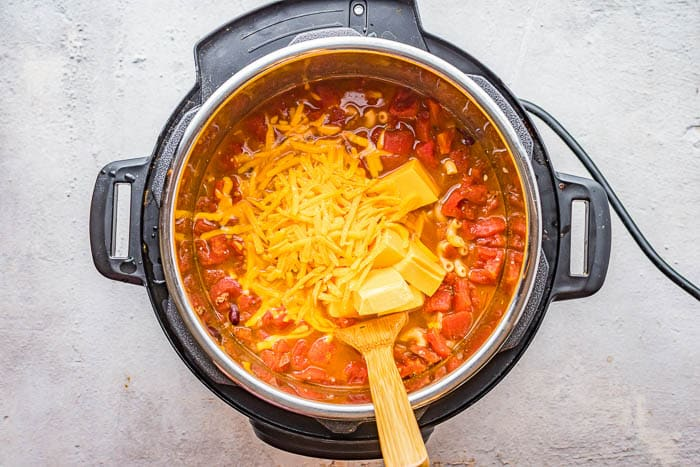 Overhead picture of adding cheese to the Instant Pot Chili Mac after the other ingredients have finished pressure cooking.