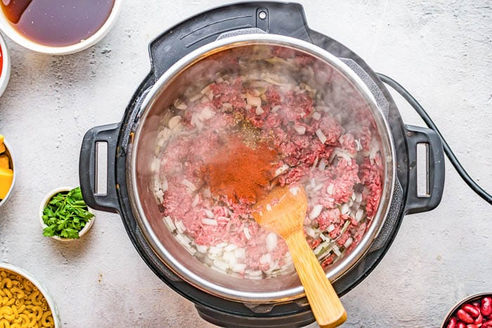 Overhead view of cooking ground beef with onions and spices in the Instant Pot pressure cooker.