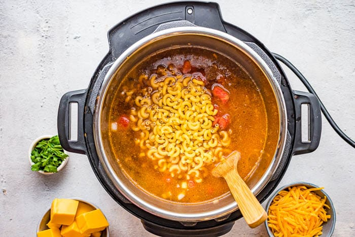 Overhead view of macaroni added to the other ingredients in the Instant Pot for Instant Pot Chili Mac.