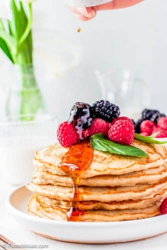 Side view of a plate with a large stack of pancakes topped with berries with maple syrup dripping down the side of the stack of pancakes.