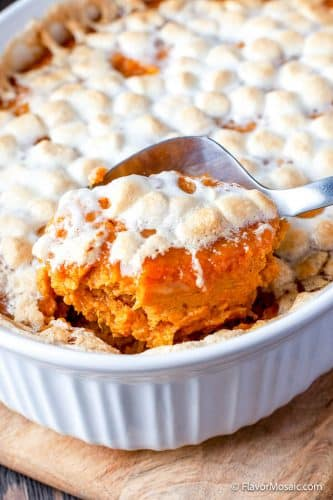 Lifting a spoonful of sweet potato casserole with marshmallows out of the casserole dish and showing all the melted marshmallows behind the spoon.