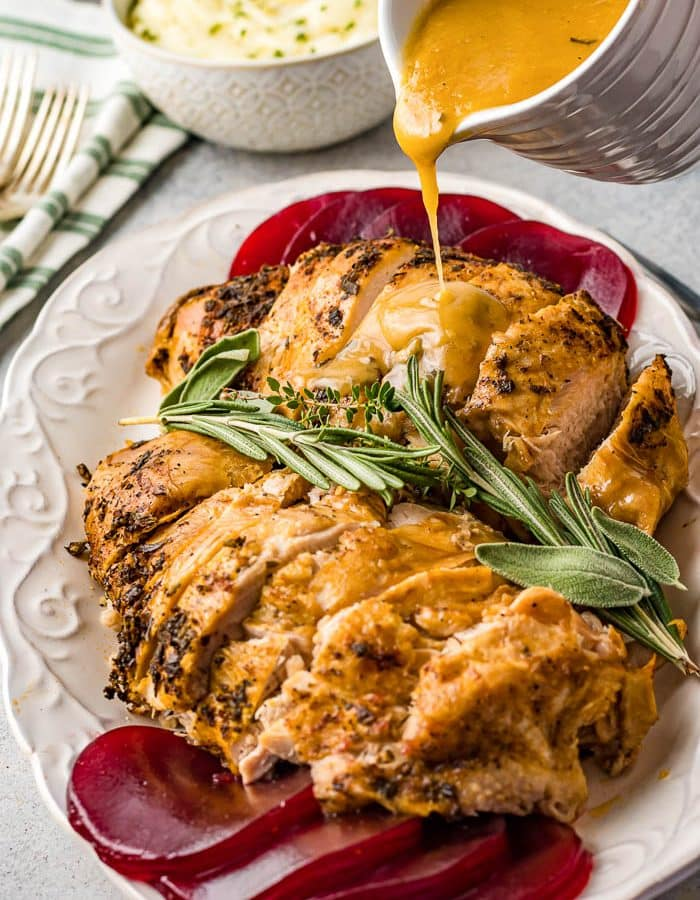 A white platter with two large turkey breasts sliced across in multiple slices with turkey gravy being poured over the top of the turkey breast. Fresh herbs and sage leaves in the middle between the two turkey breasts and cranberry sauce at each end of the oval plate. A bowl of mashed potatoes in the background.
