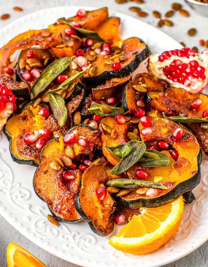 A white platter with slices of seasoned acorn squash topped with pomegranate seeds and sage leaves and garnished with orange slices and a half a pomegranate with the seeds still in it.